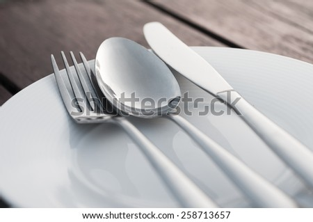 Fork spoon and knife on porcelain dish with wooden background - stock photo