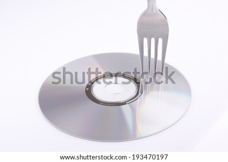 Fork touching compact disc - stock photo
