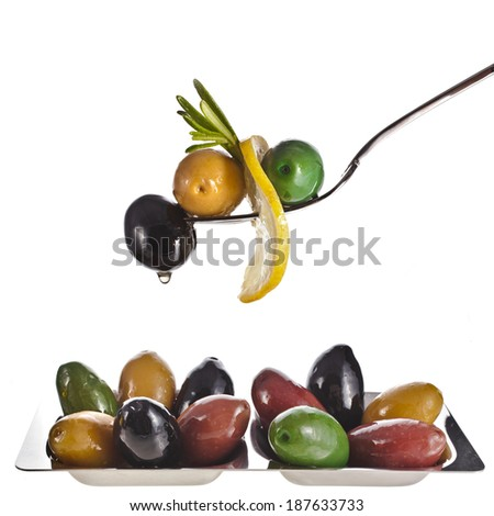 fork with colored olives and herb spice with copy space isolated on a white background  - stock photo