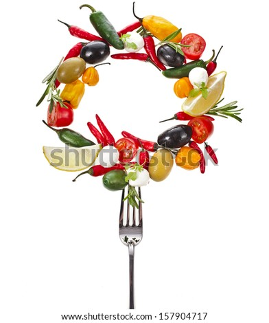 fork with falling olives and variety vegetables and herb spice, frame with copy space isolated on a white background  - stock photo