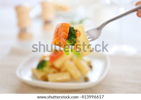 Fork with impaled boiled rigatoni pasta with salmon and broccoli, close up - stock photo