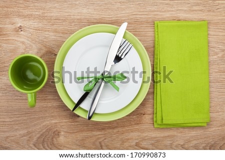 Fork with knife, blank plates, empty cup and napkin. On wooden table background - stock photo