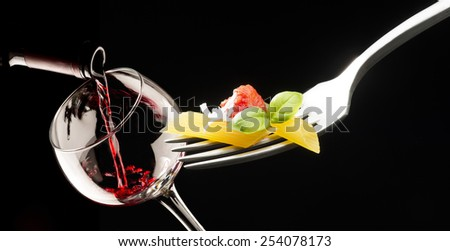fork with macaroni glass of red wine on black background - stock photo