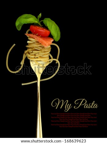 Fork with spaghetti, tomato, salmon and basil on black - stock photo