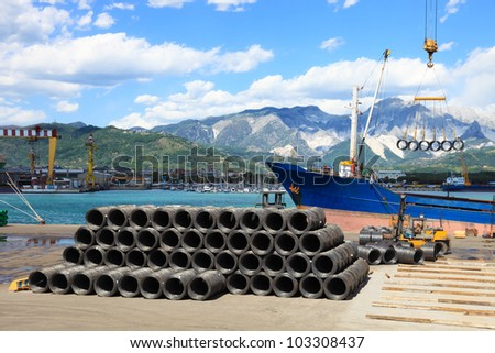 forklift and crane in harbor loading iron wire on cargo ship - stock photo