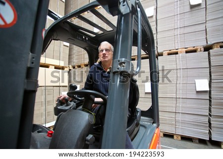 Forklift driver inside a forklift, manipulating a joystick in a warehouse full of pallets empty, plano, cardboard boxes - stock photo