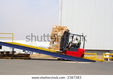 Forklift driver on loading dock - stock photo