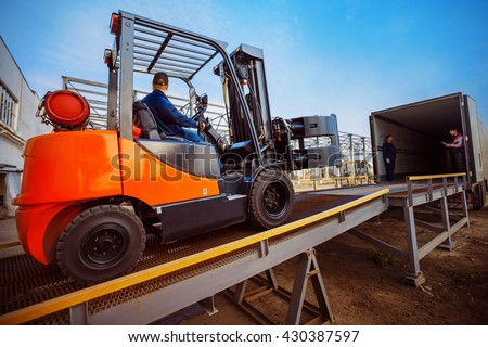 Forklift is putting cargo from warehouse to truck outdoors - stock photo