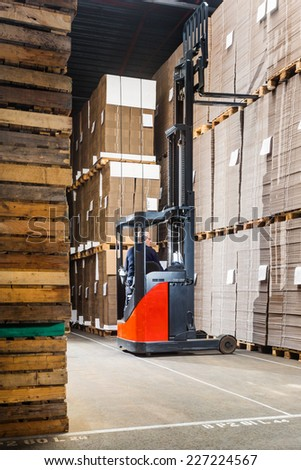 forklift lifting a pallet from the top shelf in a large warehouse - stock photo