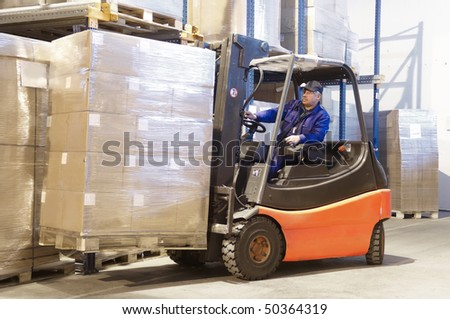 Forklift loader worker driver at warehouse - stock photo