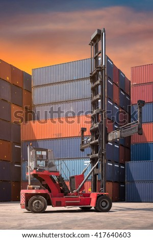 Forklift truck and cargo container in shipping yard for transportation import,export, logistic industrial with container stack in background - stock photo