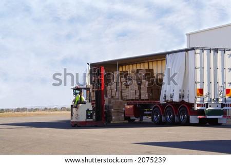 Forklift unloading truck - stock photo