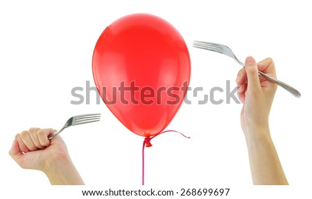 Forks about to pop a balloon isolated on white - stock photo
