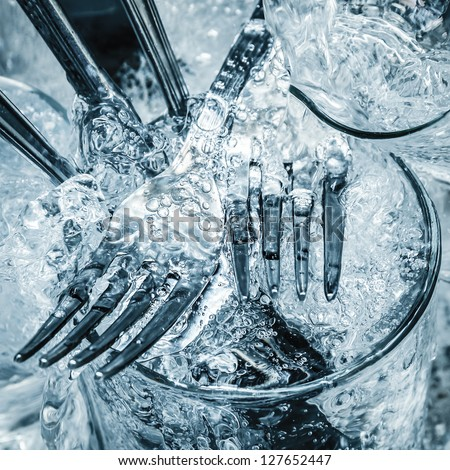 Forks,knives and glasses under a stream of water - stock photo