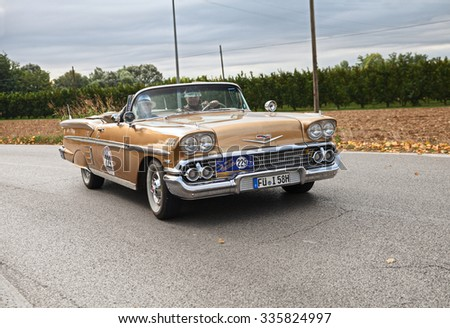 "FORLI', ITALY - SEPTEMBER 20: driver and co-driver on American vintage car Chevrolet Impala Convertible (1958) in classic car rally ""Gran Premio Nuvolari"" on September 20, 2015 in Forli, Italy