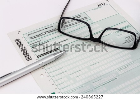 Form of income tax return with ball pen and glasses - stock photo