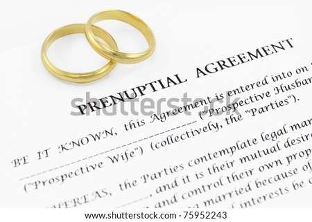 Form of prenuptial agreement with a pair of wedding rings - stock photo