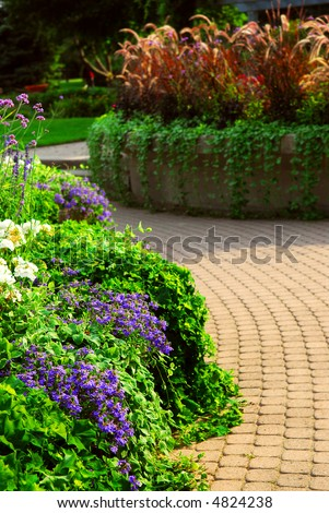 Formal garden with blooming flowers in the summer - stock photo