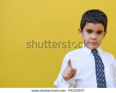 Formally dressed latin boy on a yellow wall with space for text - stock photo