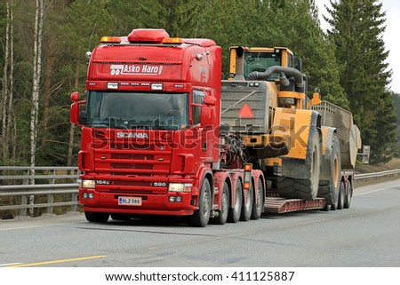 FORSSA, FINLAND - APRIL 23, 2016: Scania 164G transports heavy Volvo L350F wheel loader as wide load along road in South of Finland. - stock photo