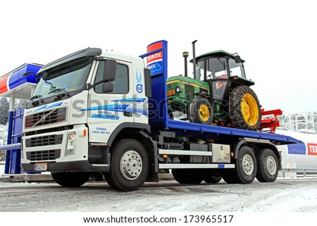 FORSSA, FINLAND - JANUARY 25, 2014: Volvo FM370 truck and John Deere 1640 tractor as cargo being refueled. Due to higher excise taxes, diesel fuel prices in Finland rise over 3 cents/litre in 2014. - stock photo