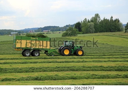 FORSSA, FINLAND - JULY 20, 2014: John Deere 6210R tractor and Krone MX 350 GL forage wagon collecting silage. Use of wagon instead of trailed forage harvester offers significant benefits. - stock photo