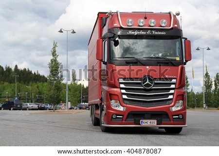 FORSSA, FINLAND - JUNE 21, 2015: Red Mercedes-Benz cargo truck drives through asphalt yard of a truck stop. In February 2016 Mercedes-Benz Trucks has the market share of 18,4 per cent in Finland.  - stock photo