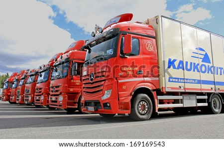 FORSSA, FINLAND - SEPTEMBER 22, 2013: Fleet of red Kaukokiito long haulage trucks. Kaukokiito is Finlands leading private transport system with a network over 1000 vehicles. - stock photo