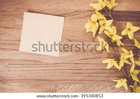 forsythia flowerd twig on a natural wood surafce - blank memo copy space - stock photo