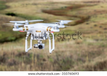FORT COLLINS, CO, USA, AUGUST 28, 2015:  Airborne radio controlled Phantom 3 quadcopter drone flying with a camera over prairie. - stock photo