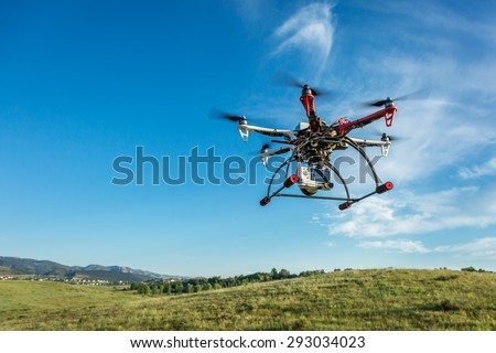 FORT COLLINS, CO, USA, June 28, 2015:  DJI  F550 Flame Wheel  hexacopter drone with Sony A6000 camera flying over foothills prairie, - stock photo
