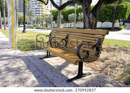 FORT LAUDERDALE, FL, USA - APRIL 7, 2014: A wood bench on a sunny day in front of tropical Galt Ocean Mile Drive with tall residential buildings trees and foliage.  A partially shaded relaxing bench.  - stock photo