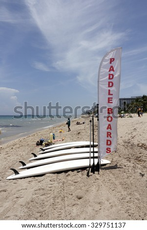 Fort Lauderdale, FL, USA - June 25, 2014: Five white paddle boards for rent on the beach with a red and white banner sign that says paddle boards. There are many people, trees and buildings - stock photo