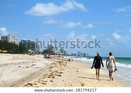 FORT LAUDERDALE, FL, USA - May 18, 2015: Tourist walking along the surf's edge on Fort Lauderdale Beach.  - stock photo