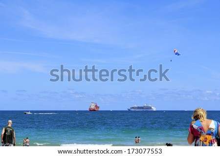 FORT LAUDERDALE, FLORIDA - APRIL 8, 2013: Colorful variety of various boats, people and parasailer off the shore of Fort Lauderdale, Florida beach on a warm bright blue sky spring day in the tropics.  - stock photo