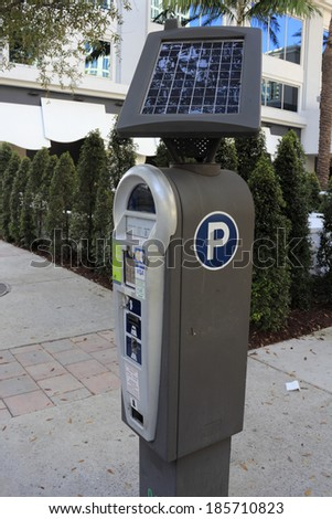 FORT LAUDERDALE, FLORIDA - MARCH 1, 2014: Closeup of a solar powered parking meter that collects various forms of payment for parking on the street in downtown with building and foliage in the day.  - stock photo
