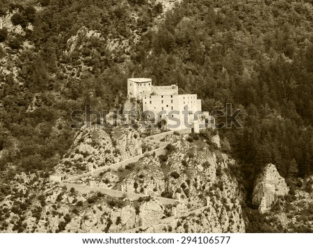 Fortress on the cliff over the medieval town of Entrevaux. (Alpes-de-Haute-Provence, France) Aged photo. Sepia. - stock photo
