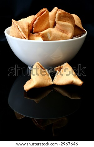 Fortune cookies in a white bowl against a black background - stock photo