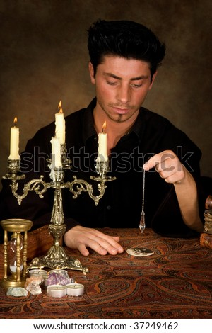 Fortune-teller holding a pendulum above a wedding photo (this photo is model released) - stock photo
