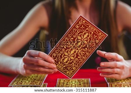 Fortune teller using tarot cards on black background - stock photo