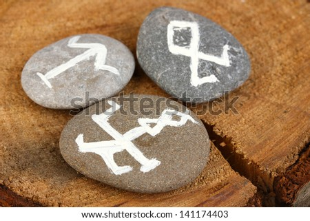 Fortune telling  with symbols on stones on wooden background - stock photo