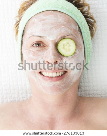 Forty year old woman with face mask and cucumber - stock photo