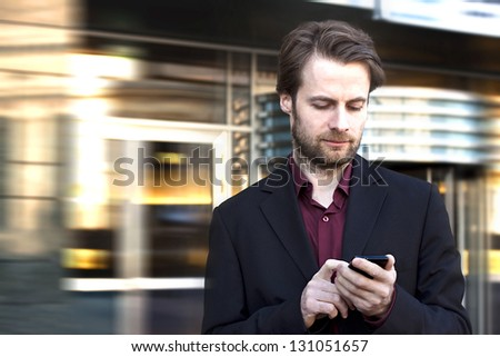 Forty years old businessman standing outside modern office building looking on a mobile phone - stock photo