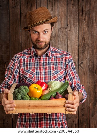 Forty years old caucasian farmer or gardener in a hat holding wooden box of fresh vegetables on rustic vintage planked wood background. Agriculture - food production, harvest. - stock photo