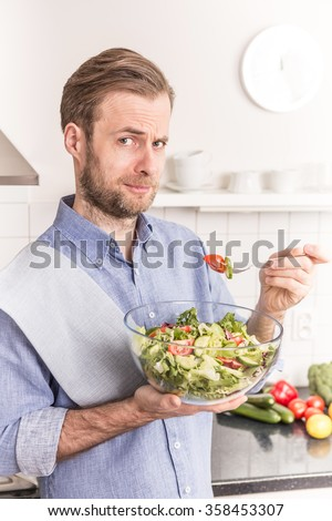 Forty years old caucasian man eating fresh vegetable salad in the kitchen. Healthy food and diet concept. - stock photo
