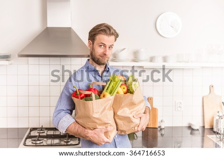 Forty years old caucasian man holding paper grocery shopping bags in the kitchen.  - stock photo