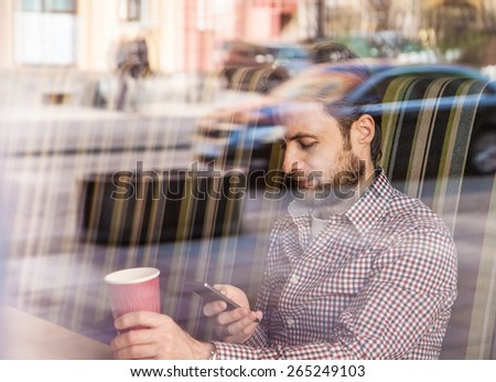 Forty years old caucasian man in casual outfit looking at mobile phone while drinking coffee in a cafe. City lifestyle - relax. - stock photo