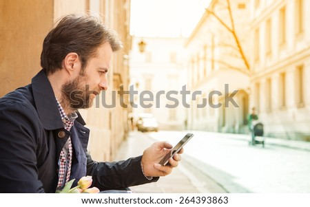 Forty years old caucasian man looking at a mobile phone. Street and city buildings as background. - stock photo