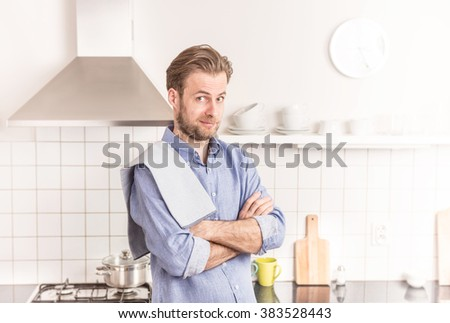 Forty years old caucasian man or chef  standing in the bright kitchen.  - stock photo