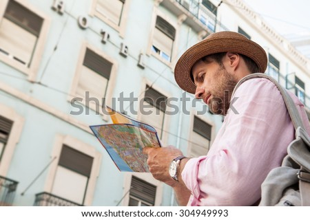 Forty years old caucasian tourist man with backpack looking at the city map outdoor. Vintage hotel as background. Summer holiday traveling. - stock photo